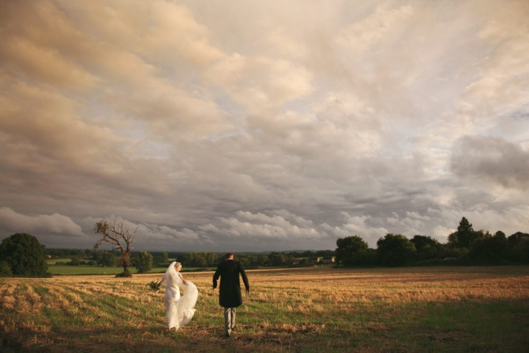 photo of a bride and groom in a field at sunset.