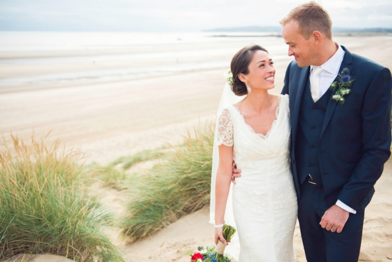 A bride and groom smile at each other during their portraits on the beach at Camber Sands.