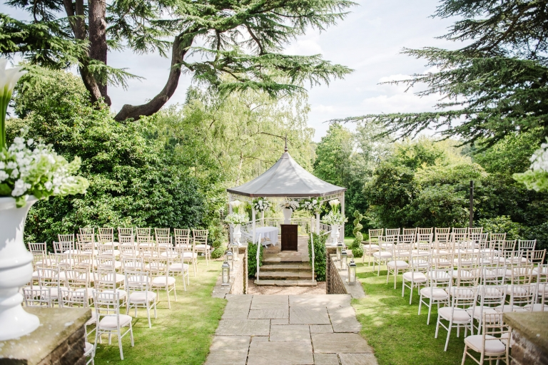 The pavilion at Pennyhill Park hotel decorated with flowers for a Surrey Summer outdoor wedding ceremony.
