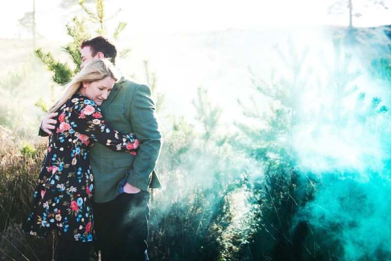 An engagement photo shoot using various coloured smoke bombs including green and blue.