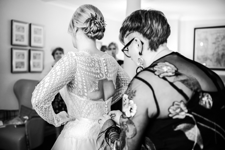Black and white candid photography of bride getting ready for her wedding.