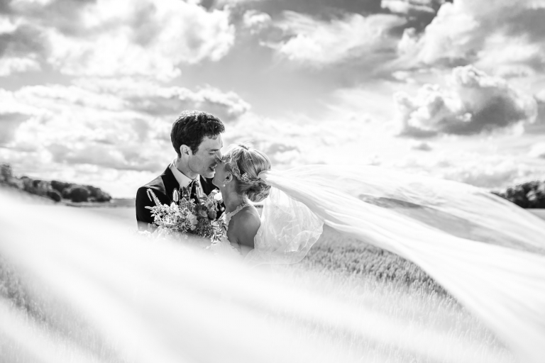 Black and white bride and groom portrait with floating veil.