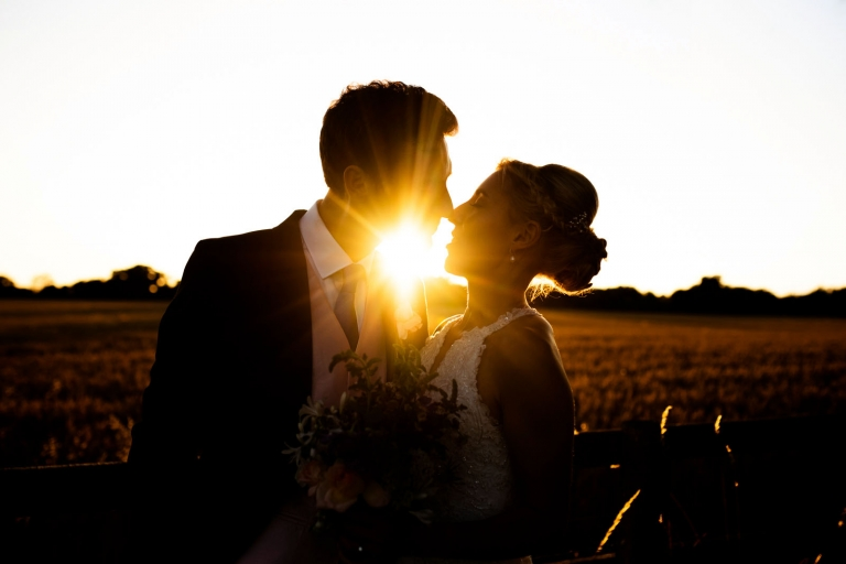 Backlit bride and groom photos at sunset.